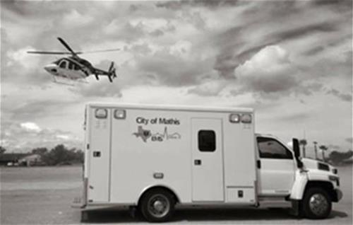 City of Mathis EMS truck with a helicopter flying overhead