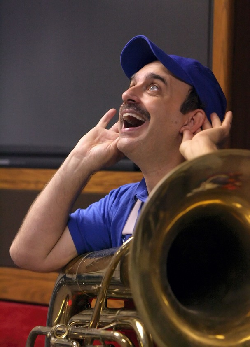 Mr. Kippy with a tuba in his lap, holding his ears